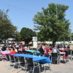 Grand Prairie Foods employees eating outside at tables during their summer party